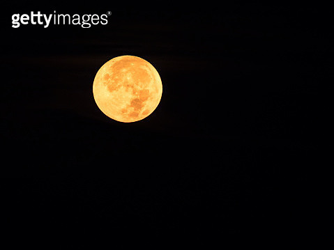 Full frame of the Supermoon of yellow color on a black sky with some high clouds of orange color. Valencia, Spain - gettyimageskorea