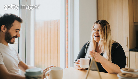Couple sit at a Dining Table and enjoy hot drinks, while chatting with each other - gettyimageskorea