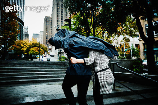 Couple running up stairs with coat over head - gettyimageskorea