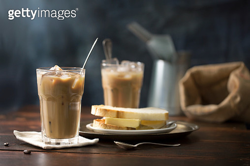 South east asian Malaysian Singaporean local traditional iced white coffee (coffee with milk) in vintage glass. Served with traditional coconut jam and butter toast and soft half boiled egg in bowl. Rustic moody wooden background. - gettyimageskorea