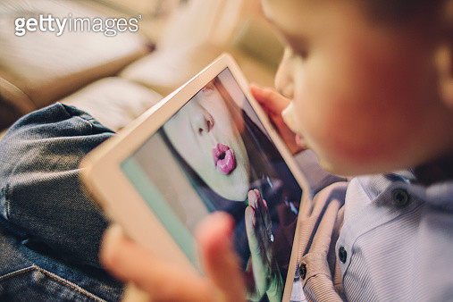 Little boy talking to his working Mother over the internet blowing her a kiss - gettyimageskorea