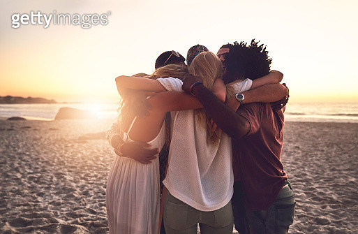Young friends hugging in a huddle on sunset summer beach - gettyimageskorea