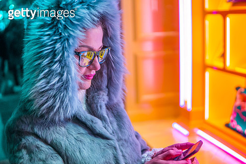 Young woman standing in front of colorful store window and texting - gettyimageskorea