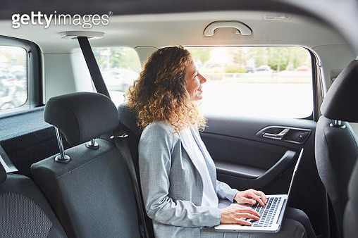 Businesswoman on the move inside a car. - gettyimageskorea