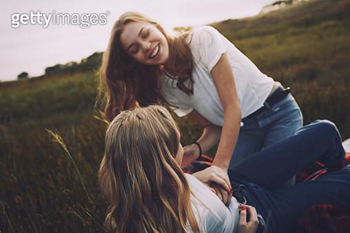 Playful teenage sisters in rural field - gettyimageskorea