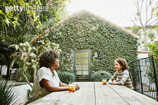 Smiling mother and daughter sitting at picnic table in backyard - gettyimageskorea