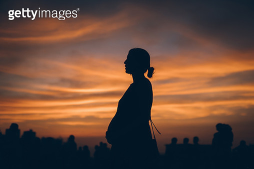 Silhouette of pregnant woman watching sunset over dramatic sky in city - gettyimageskorea