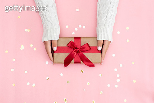 Womans hands holding gift or present box decorated confetti on pink pastel table top view. Flat lay composition for birthday or wedding. - gettyimageskorea