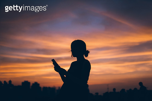 Silhouette of pregnant woman using mobile phone against dramatic sky during sunset - gettyimageskorea
