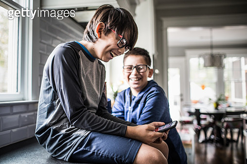 School age boys playing with smartphones - gettyimageskorea