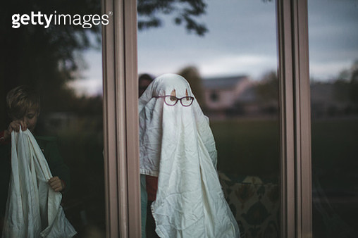 Child dresses up as a ghost wearing a white sheet with her glasses over it while a young boy gets ready to put on a sheet behind her. - gettyimageskorea