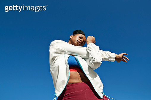 Directly below of young woman wearing sports clothing while stretching arm against clear blue sky on sunny day - gettyimageskorea