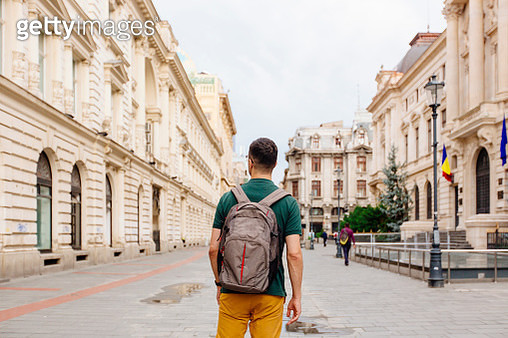 Rear view of a young man with backpack walking on the street in the old town of Bucharest - gettyimageskorea