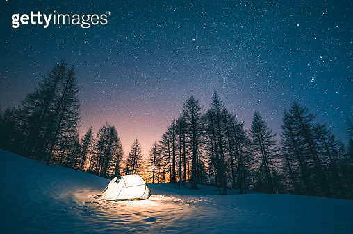 Illuminated tent at night camping on a field of snow in a winter forest under a starry sky - gettyimageskorea
