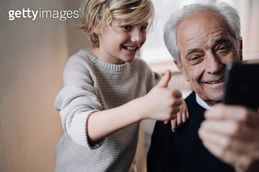 Happy grandfather and grandson taking a selfie at home - gettyimageskorea