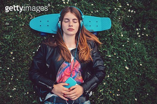 Relaxed teenage girl in the grass listening to music - gettyimageskorea