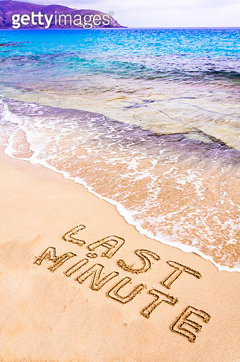 Last Minute written on sand, with waves in background, vacation concept - gettyimageskorea