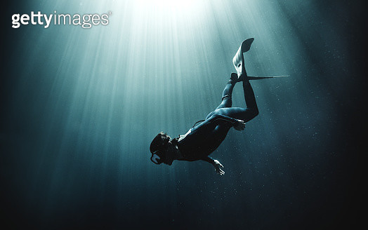 Underwater view of diver wearing wet suit and flippers, sunlight filtering through from above. - gettyimageskorea