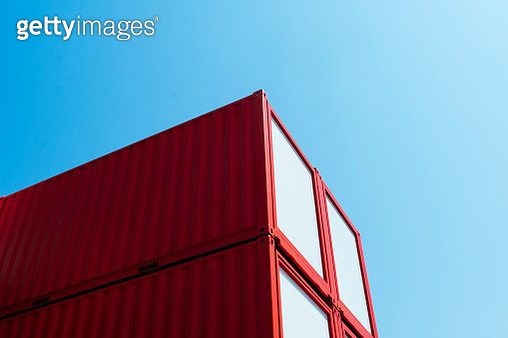 Close-up of repurposed red shipping containers with clear blue sky - gettyimageskorea