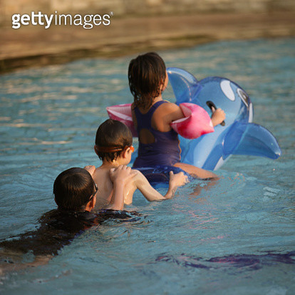 Kids playing train & dolphin balloon in the pool - gettyimageskorea