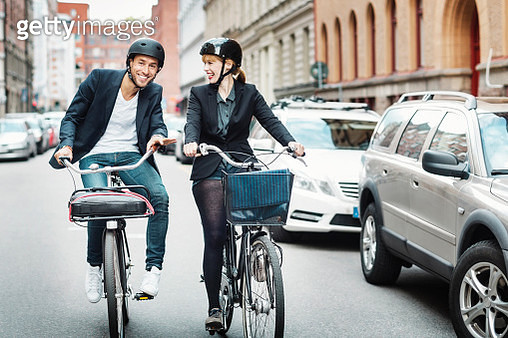 Happy business people riding bicycles on city street - gettyimageskorea