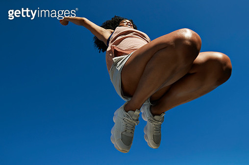 Full length of fit female athlete with arms raised jumping against clear blue sky on sunny day - gettyimageskorea