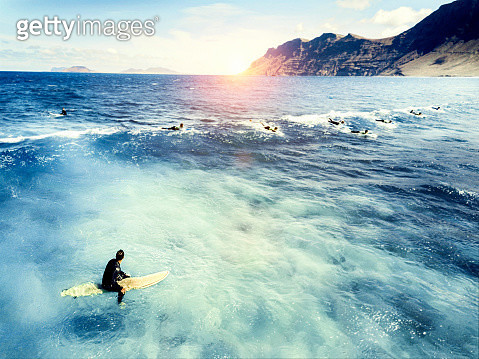Young man sitting on surf board in sea - gettyimageskorea