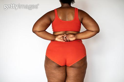 Rear view of a chubby woman in underwear - gettyimageskorea