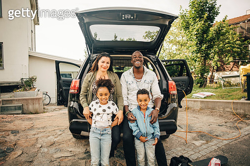 Portrait of smiling multi-ethnic family leaning on car trunk in front yard - gettyimageskorea