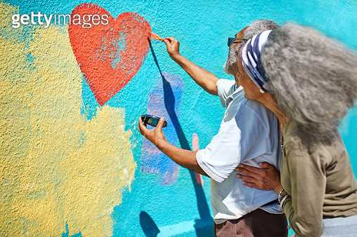 Senior couple painting heart-shape mural on sunny wall - gettyimageskorea