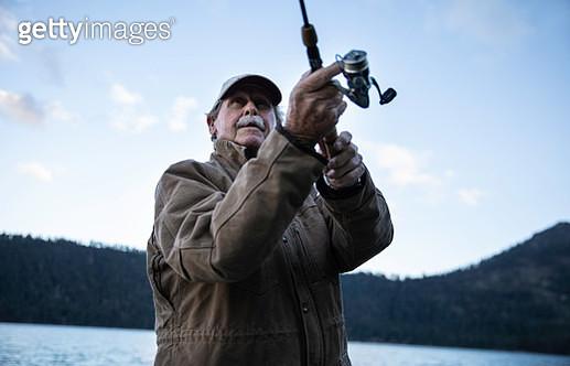 Active Senior Man Trout Fishing Alone on a Mountain Lake - gettyimageskorea