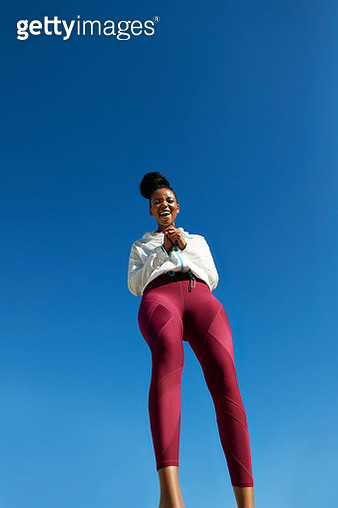 Directly below shot of cheerful young woman wearing sports clothing while standing against clear blue sky on sunny day - gettyimageskorea