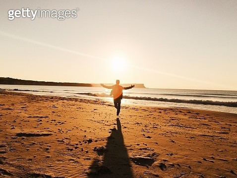 Man running with his arms spread at the beach during sunset - gettyimageskorea