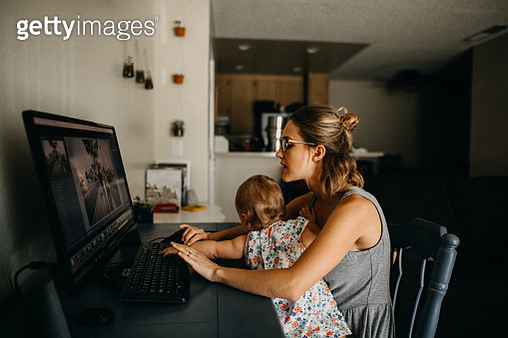 Multitasking working mother holding baby and typing on computer - gettyimageskorea