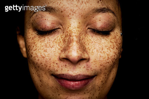 Close up of freckles on mixed race woman with her eyes closed - gettyimageskorea