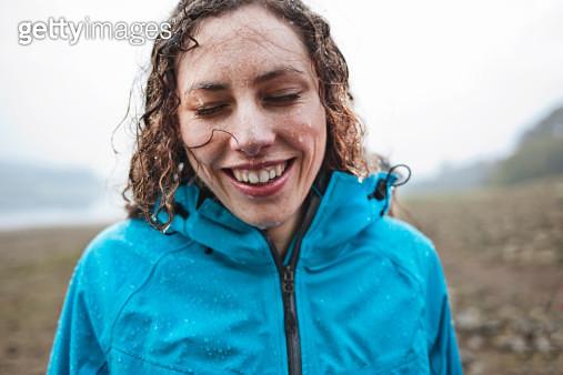 femalesmiling in the rain - gettyimageskorea