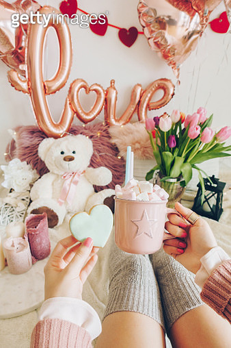 Valentine's day concept: woman's hands holding a cup of cocoa with marshmallows and a heart shaped cookie. Foil balloons decorations in the background. - gettyimageskorea