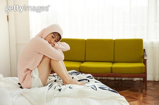 침대에 앉아 우울해하는 여성 - gettyimageskorea