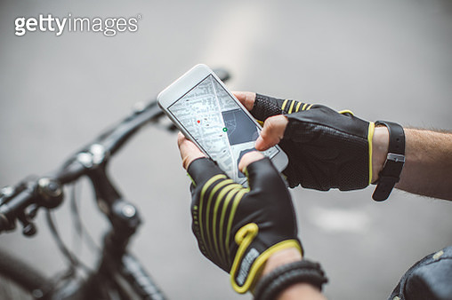Bicycle delivery commuter with road bicycle in the city. He cycling and using mobile phone to find fastest way - gettyimageskorea