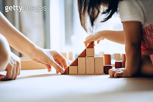 Close up of mother and little daughter sitting on the floor playing with wooden building blocks together and enjoying family bonding time at home - gettyimageskorea