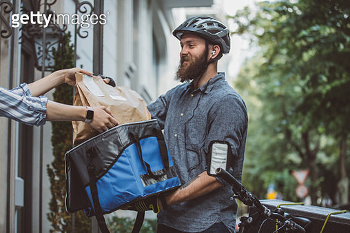Bicycle delivery commuter with road bicycle delivering package to customer - gettyimageskorea