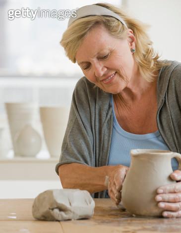 Senior woman making ceramic pot - gettyimageskorea