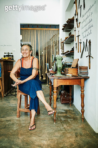 Portrait of smiling female shoemaker sitting at worktable in workshop - gettyimageskorea