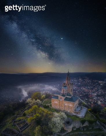 Night sky illuminated by thousands of stars glittering and drawing beautiful pictures of the wide Universe that surrounds us. A mist over the city and the ancient fortress. - gettyimageskorea