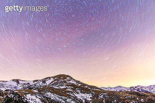 Spain, Catalonia, Gerona, Pyrenees, Star trail above snowcapped mountain range - gettyimageskorea