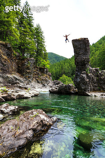 Young man jumps from high precipice into pool of water - gettyimageskorea