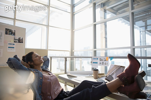 Confident female designer with feet up and hands behind head in office - gettyimageskorea