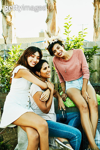 Smiling daughters embracing mother during backyard barbecue with family - gettyimageskorea