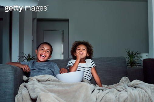 Happy siblings having popcorn while watching TV - gettyimageskorea