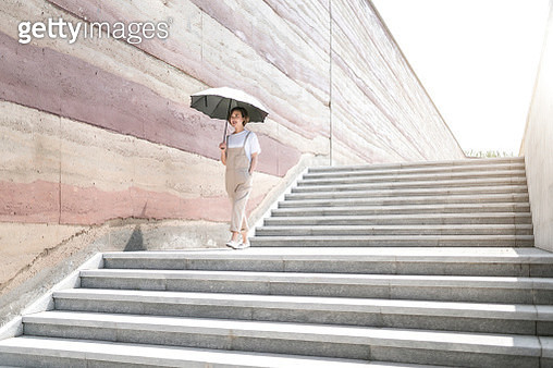 woman climbs the stairs with a bright light - gettyimageskorea